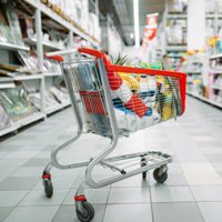 Cart full of goods in supermarket, nobody, shopping concept. Trolley with products in market, no people